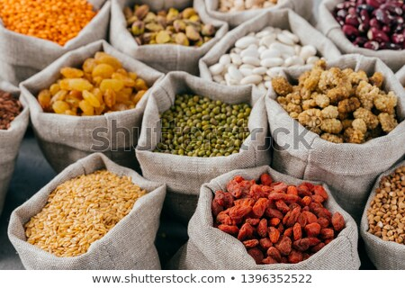 Food concept. Close up cropped shot of various kinds of natural cereals and dried fruit in sacks. Le Stock photo © vkstudio