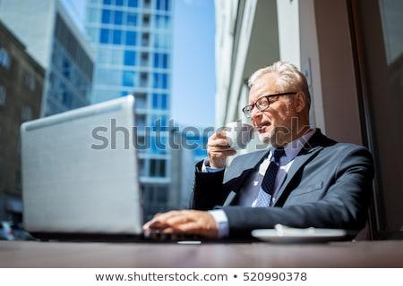 senior businessman drinking coffee on city street Stock photo © dolgachov