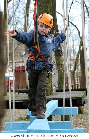 Portrait of 6 years old boy wearing helmet and climbing. Child in abstacle course in adventure playg Stock photo © galitskaya
