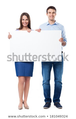 attractive smiling couple holding a blank whiteboard stock photo © stockyimages