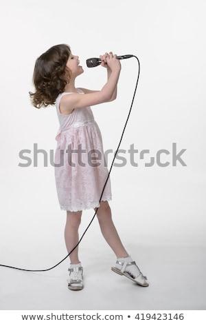 Csinos lány énekel mikrofon fekete ruha barna hajú Stock fotó © feelphotoart