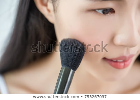 happy attractive woman applying blusher stock photo © stryjek