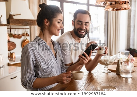 Bájos nő iszik kávé mobiltelefon otthon Stock fotó © deandrobot