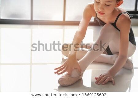 ballerina tying pointe shoes in ballet class stock photo © deandrobot