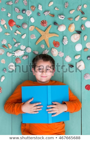 Boy with blank book laying down near sea shells Stock photo © ozgur
