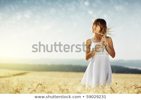 Stock photo: smiling young woman in white dress on cereal field