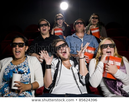 woman in 3d glasses watching a scary movie and eating popcorn stock photo © studiostoks