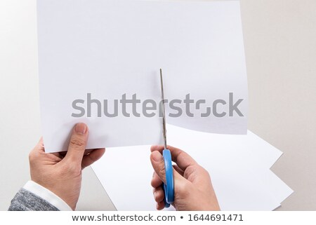 Hand of a woman holding pen with paper cut out in background Stock photo © wavebreak_media
