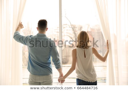 happy couple by the window opening curtains at new home stock photo © dashapetrenko