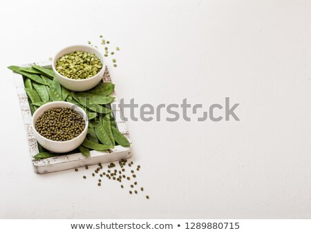 bowl of mung beans and split peaswith raw organic mangetout in vintage wooden box on white stone ki stock photo © denismart
