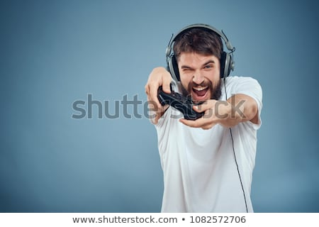 Portrait of happy smiling guy playing video games on computer, w stock photo © deandrobot
