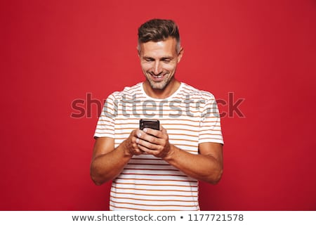 Image of unshaved man in striped t-shirt smiling and holding sma Stock photo © deandrobot