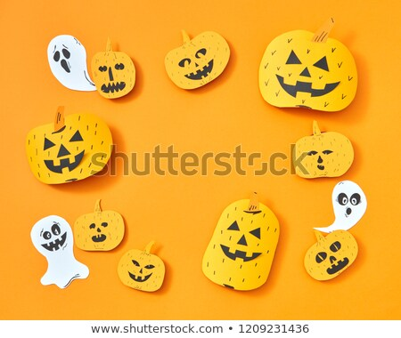 Postcard for Halloween handcraft of paper ghosts and pumpkins with scary faces on a branch presented Stock photo © artjazz