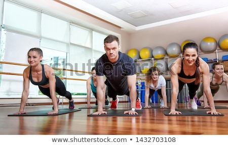 Cropped image of motivated sports woman doing exercise with barbell Stock photo © deandrobot