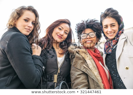 Group of four cheerful friends spending time together Stock photo © deandrobot