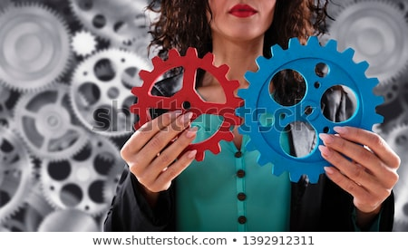 Stok fotoğraf: Businesswoman Tries To Connect Gears Pieces Concept Of Teamwork Partnership And Integration