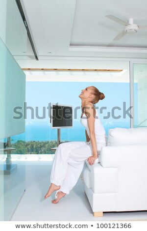 Chic young woman sitting by the ocean. Stock photo © lovleah