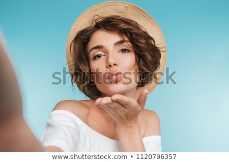 Beautiful woman isolated over blue background take a selfie by mobile phone. Stock photo © deandrobot