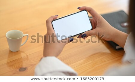 Contemporary young woman with smartphone surfing in online shop Stock photo © pressmaster