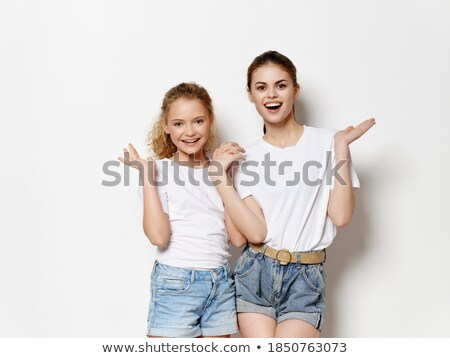 A family of two people mom and daughter in white dresses are sitting on the floor under the New Year Stock photo © ElenaBatkova