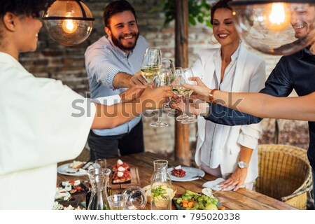 People cheering with white wine and rising glasses on celebratio Stock photo © dashapetrenko