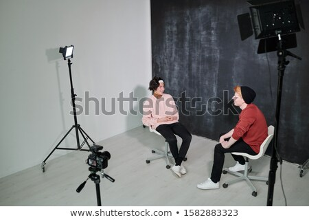 Kettő boldog fiatal ül székek egyéb Stock fotó © pressmaster