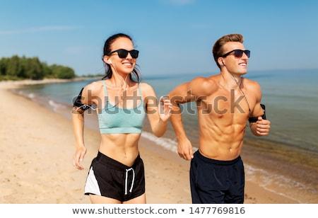 couple with earphones running along on beach Stock photo © dolgachov