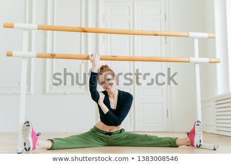 Skillful female ballerina demonstrates leg splits near barre, has flexible body, smilles gladfully,  Stock photo © vkstudio