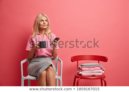Thoughtful pleased woman with dreamy look, holds mobile phone, sends text message, wears white forma Stock photo © vkstudio