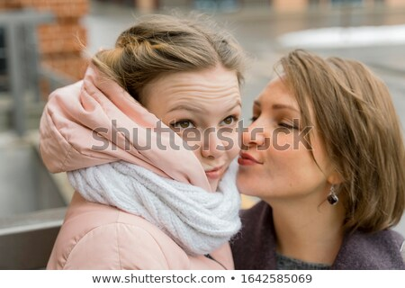 Teenage daughter not happy from her mother kissing her  Stock photo © tab62