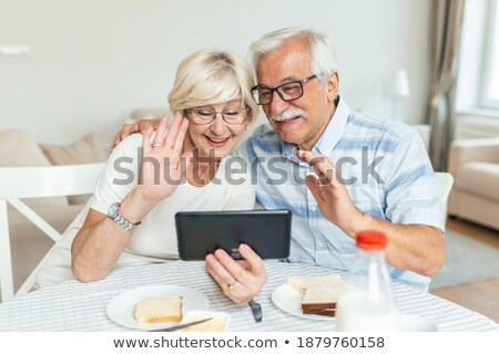 Woman chatting on a mobile while reading a tablet Stock photo © juniart