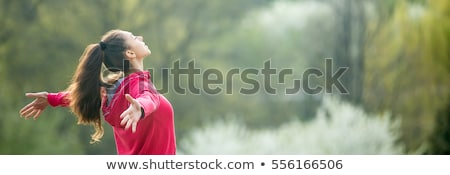 Happy young woman with opened hands feeling free outdoors Stock photo © deandrobot