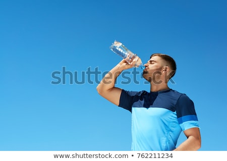 Stock photo: Handsome young man drinking after running.