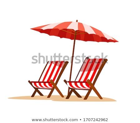 sun umbrellas and deckchairs on empty beach stock photo © amok