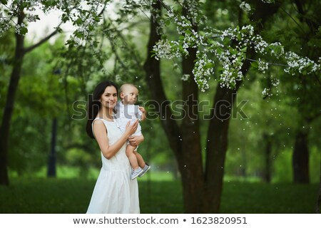 Mother with son to keep for hands in garden in spring Stock photo © Paha_L