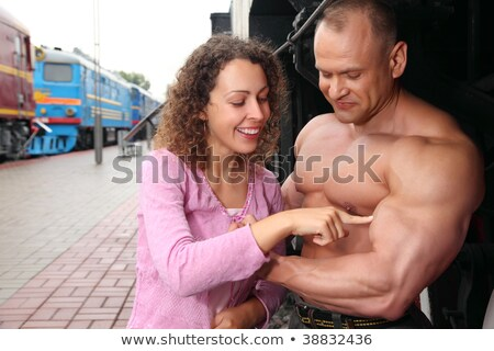 young woman  touches by finger  biceps of athlete Stock photo © Paha_L