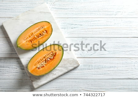 Cantaloupe melon slices on rustic wooden table, top view Stock photo © stevanovicigor