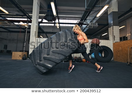 Concentrated young woman athlete working out Stock photo © deandrobot