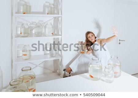 Woman with fish in jar sitting and showing stop gesture Stock photo © deandrobot