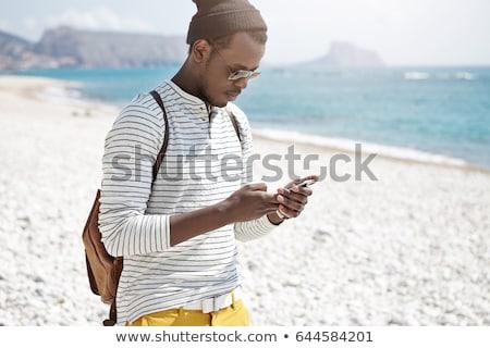 male tourist using mobile phone at seaside on summer holiday stock photo © stevanovicigor