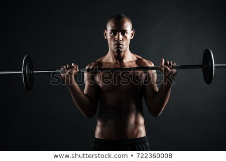 portrait of young muscular afro american man holding barbell stock photo © deandrobot