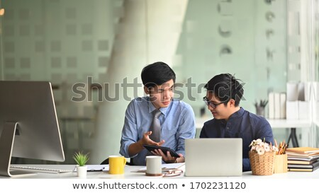two colleagues conferring over plans stock photo © is2
