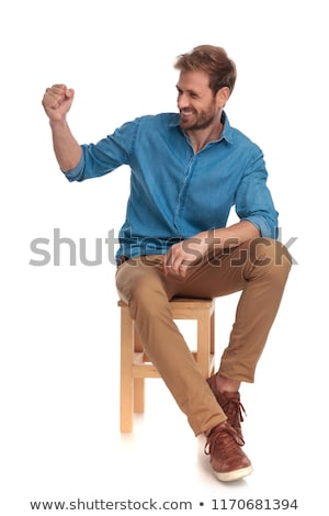 casual man sitting on wooden chair looks to side  Stock photo © feedough