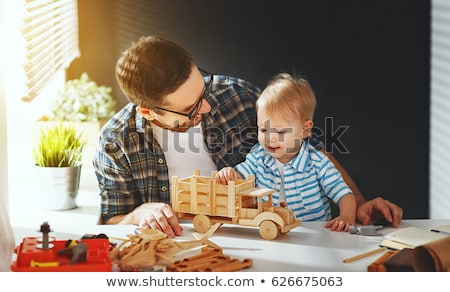 happy little boy with wood plank at workshop Stock photo © dolgachov