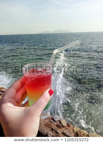 A glass with a colored puff cocktail in a female hand against th stock photo © TanaCh