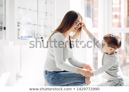 Woman choosing new glasses out of shelf in optician store Stock photo © Kzenon