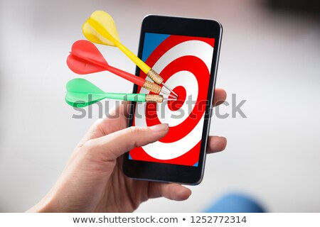 person holding cellphone with darts on target stock photo © andreypopov