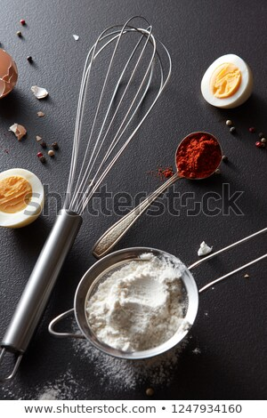Сток-фото: A Set Of Knife With Pepper Sieve With Flour Metal Whisk And Boiled Eggs On A Black Concrete Backgr