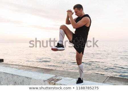 handsome young sports man standing on the beach make stretching exercises stock photo © deandrobot