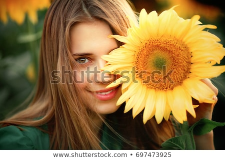outdoors portrait of smiling woman standing in field of sunflowers stock photo © elenabatkova